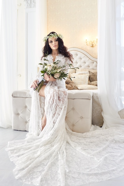 Noiva linda em lingerie e com uma coroa de flores na cabeça, na manhã antes do casamento. camisa de noite branca da noiva, preparando-se para a cerimônia de casamento. garota sexy na cama Foto Premium