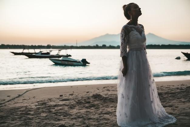 Noiva linda na praia atrás do mar ao pôr do sol Foto gratuita
