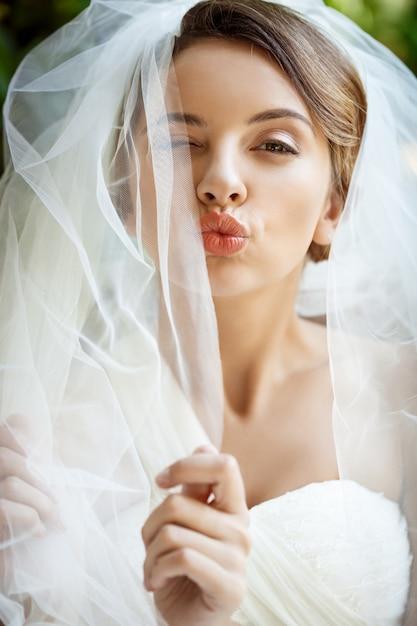 Noiva linda no vestido de casamento e véu piscando, mandando beijo. Foto gratuita