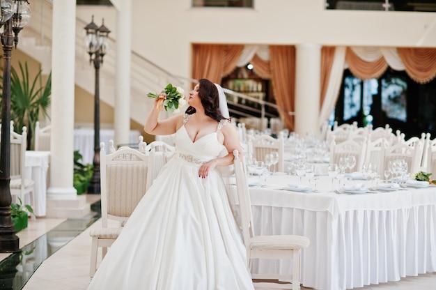 Noiva morena de seios grandes com buquê de casamento colocado em mesas de fundo de salão de casamento Foto Premium
