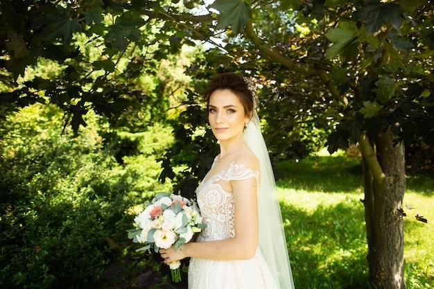 Noiva no vestido de casamento da fôrma no fundo natural. um, mulher bonita, retrato, parque Foto Premium