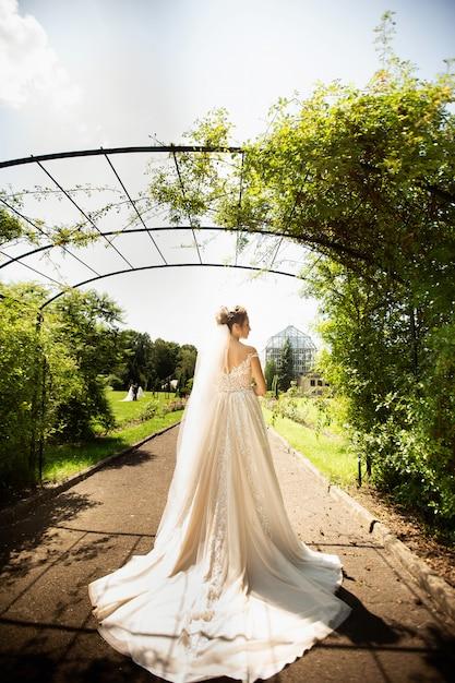 Noiva no vestido de casamento da fôrma no fundo natural. um retrato bonito da mulher no parque. vista traseira Foto Premium