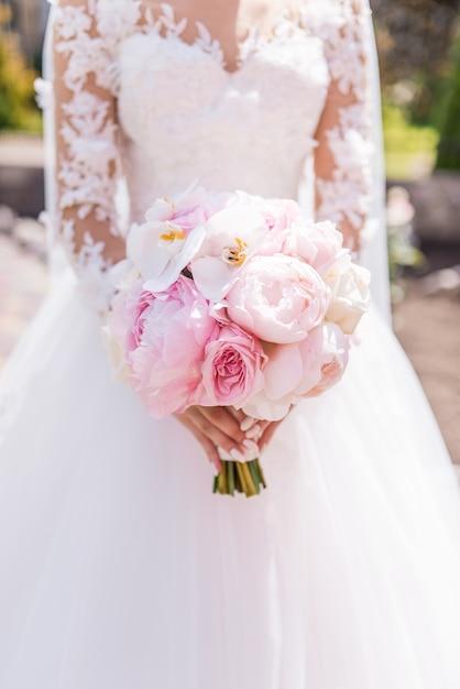 Noiva no vestido rico contém buquê de noiva rosa de orquídeas e peônias Foto gratuita