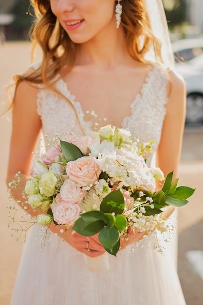 Noiva que prende um ramalhete das belas artes do casamento em cores cor-de-rosa pastel. fechar-se. Foto Premium