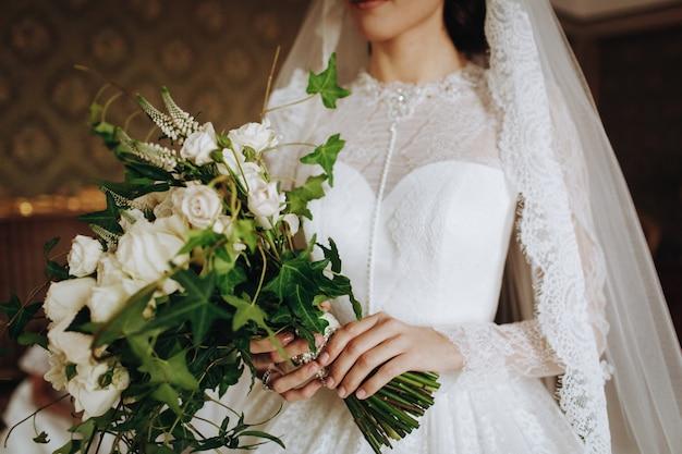 Noiva, segura, buquê casamento, de, flores brancas, em, dela, mão Foto gratuita