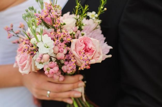 Noiva segura um buquê de casamento nas mãos, o noivo abraça ela Foto Premium