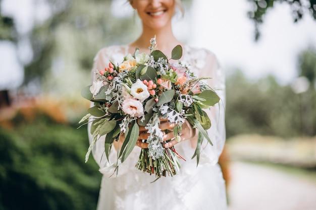 Noiva segurando seu buquê no dia do casamento Foto gratuita