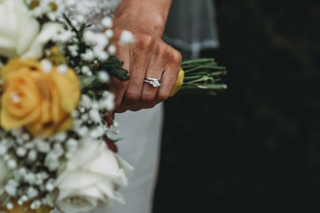 Noiva usando um anel de casamento, segurando seu buquê Foto gratuita