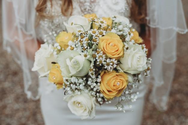 Noiva usando um vestido de noiva, segurando seu buquê tradicional Foto gratuita