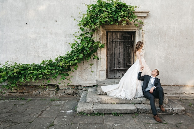 Noivas bonitas são fotografadas perto da casa velha Foto gratuita
