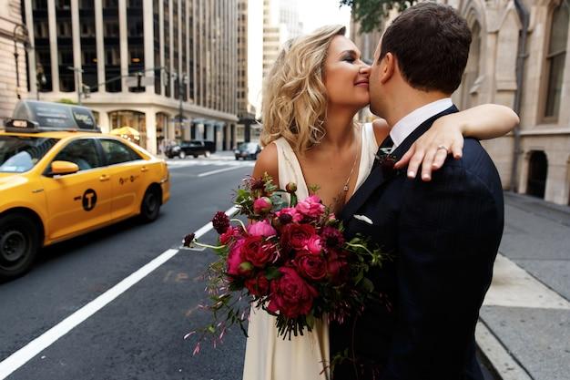 Noivo abraça linda noiva com buquê vermelho em pé na rua da cidade de nova york Foto gratuita