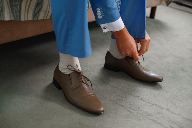 Noivo amarrou os cadarços nos sapatos marrons close-up. homem de negócios está pendurando sapatos indoor no quarto de hotel de manhã ... melicio mãos e par de sapatos masculinos de couro. reunião do noivo. Foto Premium