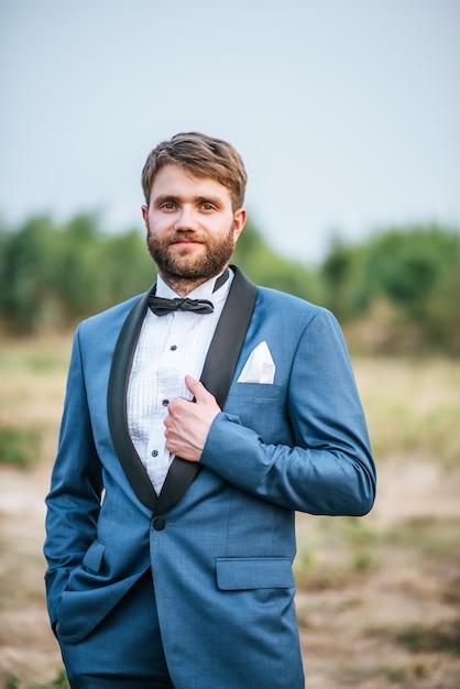 Noivo bonito no terno de casamento postando no parque Foto gratuita
