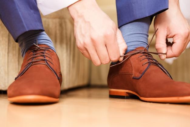 Noivo colocando seus sapatos de casamento. Foto Premium