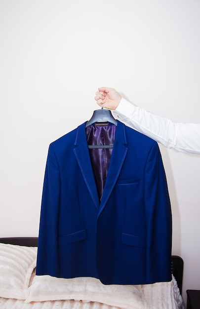 Noivo de casaco azul pendurado no cabide Foto Premium