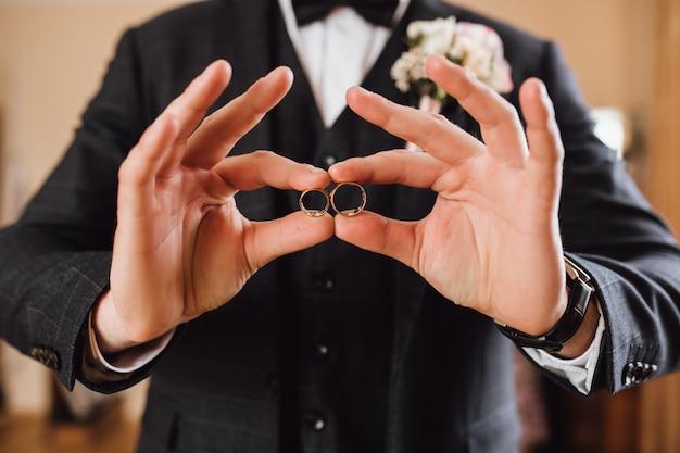 Noivo demonstra dois anéis de casamento, sem rosto Foto gratuita