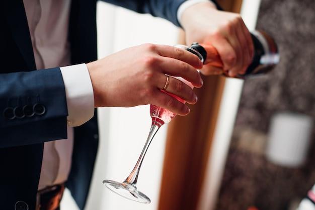 Noivo derrama champanhe vermelho de uma garrafa em um copo Foto Premium