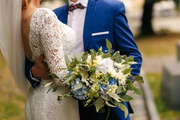 Noivo detém lindo buquê enquanto ele abraça a cintura da noiva Foto Premium