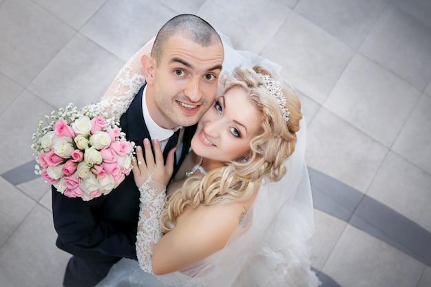 Noivo e a noiva com um buquê de rosas em uma mão olhar para cima Foto Premium
