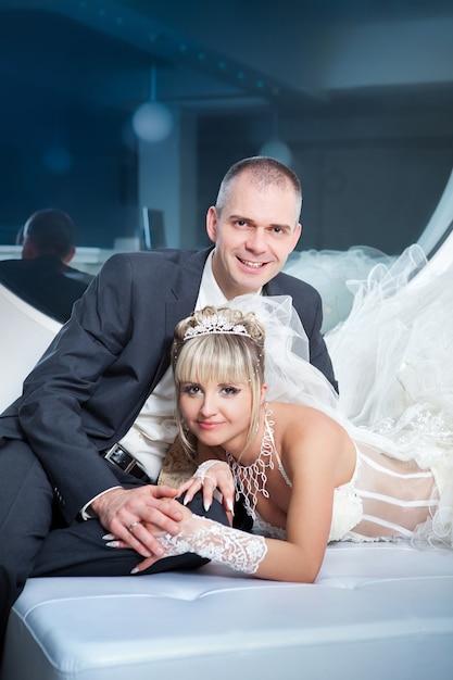 Noivo e a noiva deitar em uma cama Foto Premium