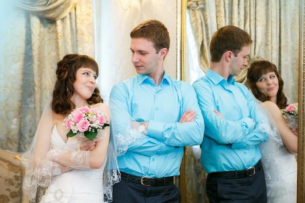 Noivo e a noiva estão perto de um espelho com uma moldura de ouro Foto Premium