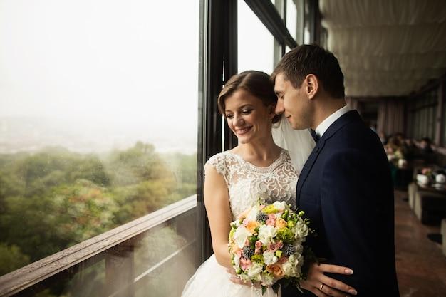 Noivo e noiva com um buquê de pé no terraço com vista para a natureza verde Foto Premium