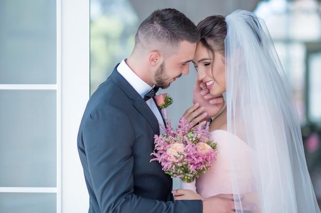 Noivo e noiva em um vestido rosa abraçam-se com o amor de pé em um quarto Foto gratuita