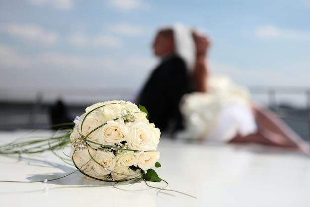 Noivo e noiva feliz sentar no iate com um buquê de casamento Foto Premium