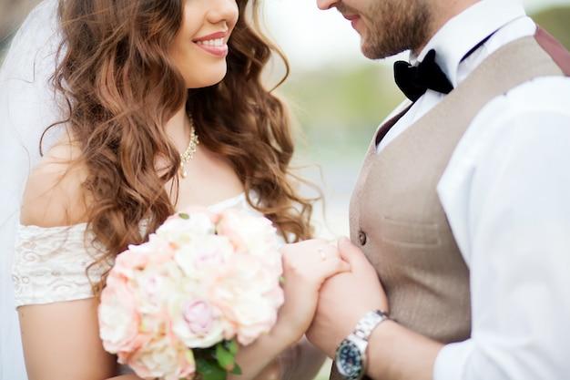 Noivo e noiva segurando buquê de pequenas rosas Foto Premium