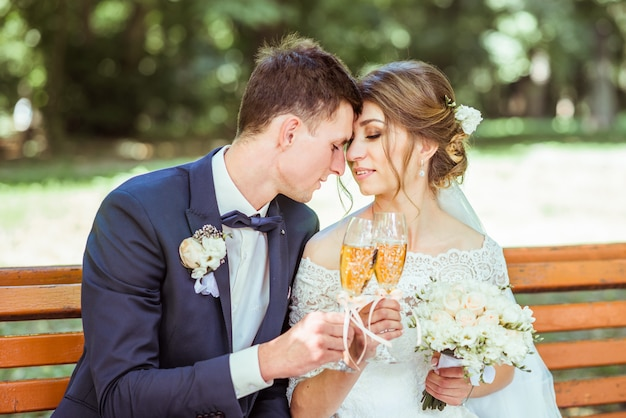 Noivo e noiva senta-se no parque Foto Premium