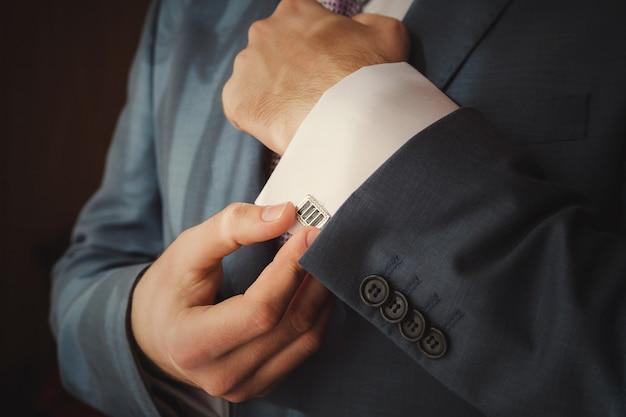 Noivo está colocando em botões de punho como ele se veste com roupa formal close-up Foto Premium