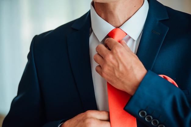 Noivo está segurando as mãos na gravata, terno de casamento Foto Premium