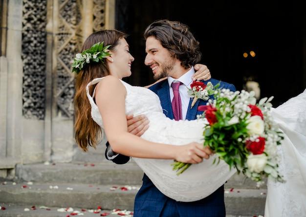 Noivo levantando sua linda noiva Foto Premium