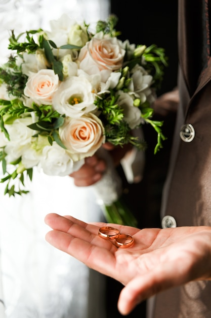 Noivo segurando um anel de ouro Foto Premium