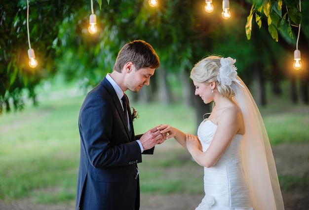 Noivo usa anel para noiva sob o arco de lâmpadas de iluminação Foto Premium
