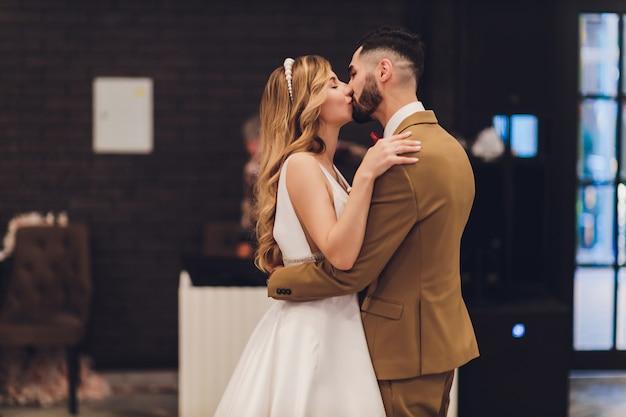 Noivos felizes à moda que levantam na palavra grande do amor na luz da noite na recepção de casamento fora. lindo casal de noivos se divertindo no parque à noite. Foto Premium
