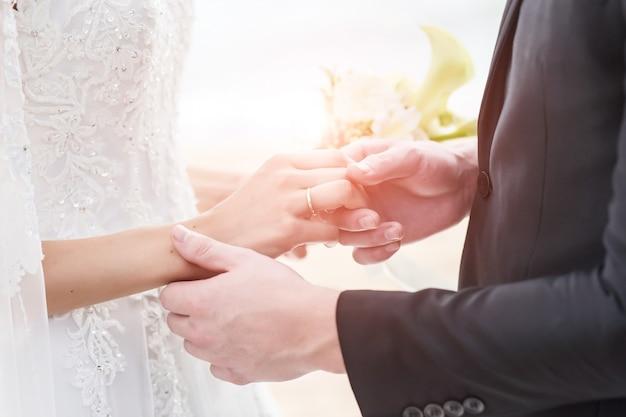 Noivos que guardam as mãos com alianças de casamento no fundo do mar e do sol. Foto Premium