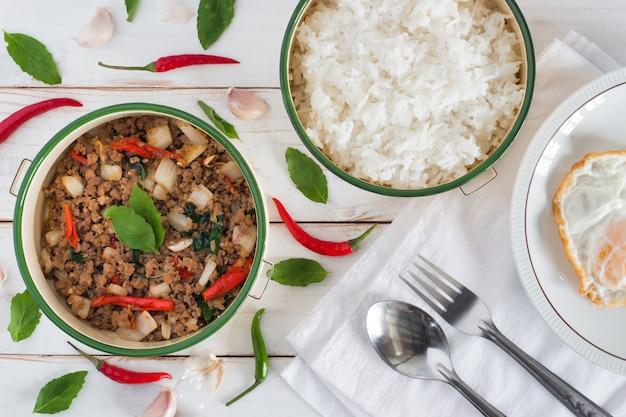 Nome de comida tailandesa pad ka prao, vista superior imagem de carne de porco frito com folhas de manjericão ao lado ter arroz cozido e ovo frito no prato definido na mesa de madeira branca Foto Premium