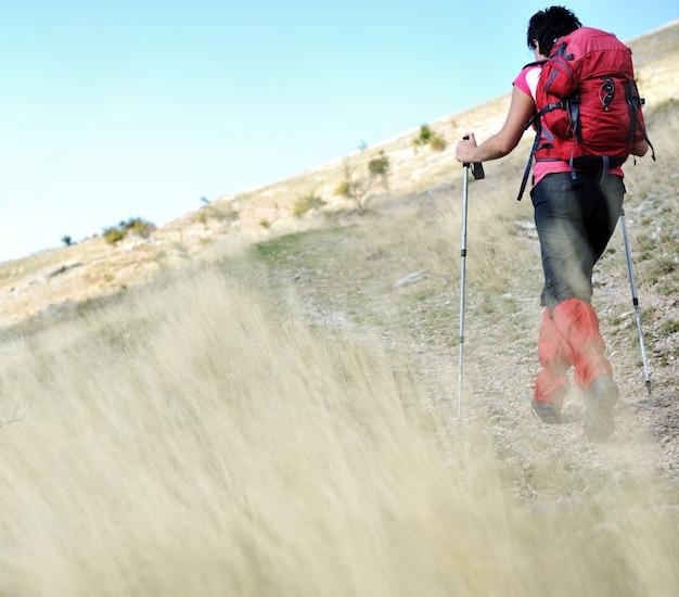 Nordic walking in mountains, hiking woman in grass Foto Premium