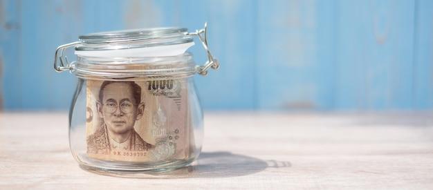 Nota de 1000 baht tailandês em frasco de vidro. dinheiro, negócio Foto Premium