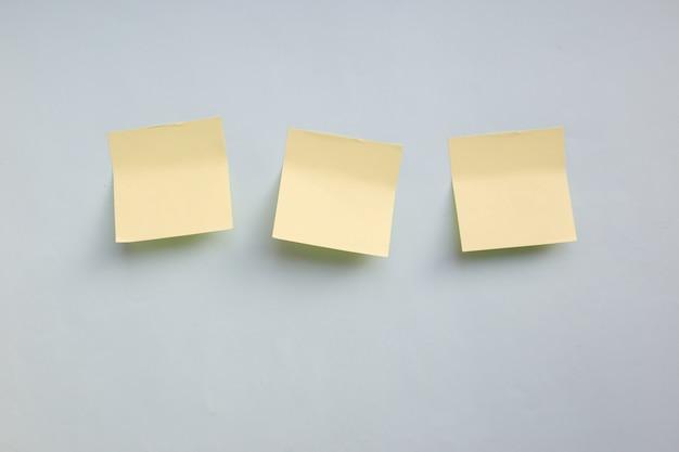 Nota de adesivos de papel amarelo três com espaço de cópia sobre fundo azul Foto Premium