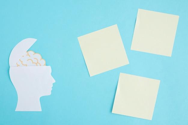 Notas auto-adesivas em branco com o cérebro na cabeça aberta sobre fundo azul Foto gratuita