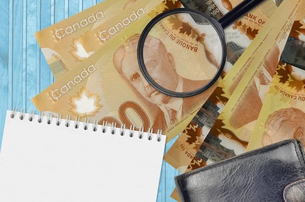 Notas de 100 dólares canadenses e lupa com bolsa preta e bloco de notas. conceito de dinheiro falso. procure diferenças nos detalhes em notas de dinheiro para detectar dinheiro falso Foto Premium