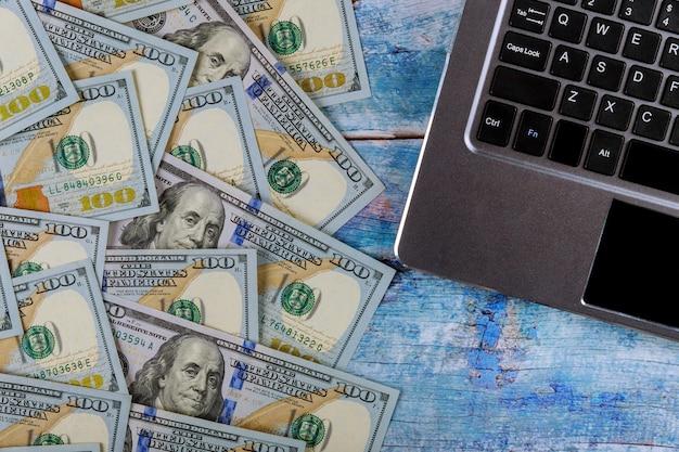 Notas de 100 dólares de papel-moeda no conceito financeiro de teclado de laptop Foto Premium