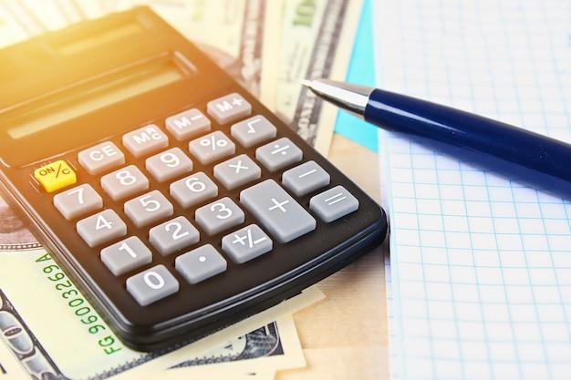 Notas de cem dólares dos estados unidos, calculadora, contas. Foto Premium