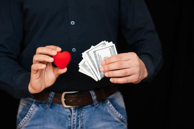 Notas de dinheiro e um coração vermelho nas mãos de um homem Foto Premium