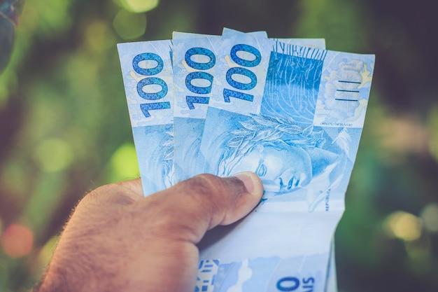 Notas de dinheiro (reais) na mão. desfoque de fundo. Foto Premium