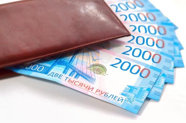 Notas de dois mil rublos russos na carteira de couro marrom no fundo branco. Foto Premium