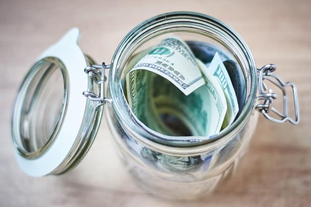 Notas de dólar dos eu em um frasco de vidro no fundo de madeira. poupar dinheiro e investimento conceito Foto Premium