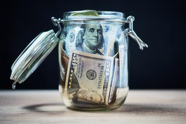 Notas de dólar dos eua no frasco de vidro. poupar dinheiro e investimento conceito Foto Premium